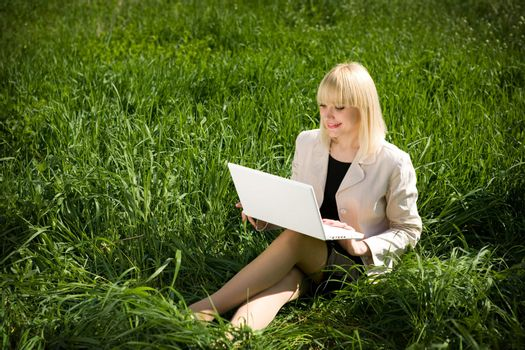pretty girl with otebook on the grass