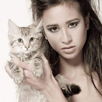 Studio portrait of a beautiful mixed race, vietnamese girl and a main coone kitten