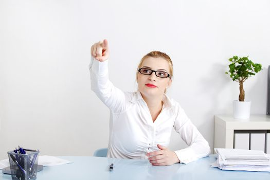 Pretty businesswoman pushing an abstract button in the office.
