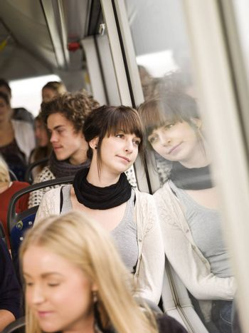 Young woman on the bus with large group of people