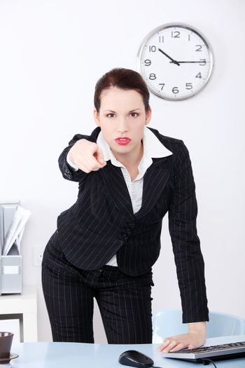 Pretty caucasian businesswoman pushing abstract button in the office.