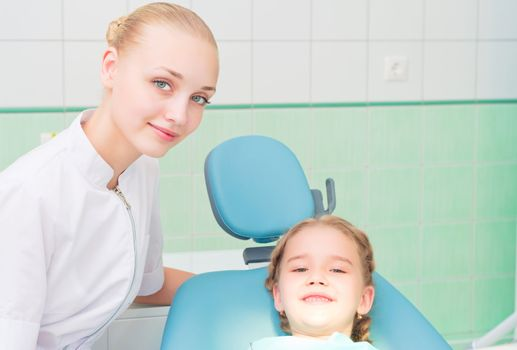 young doctor woman and girl in dentist office, regular visits to the dentist