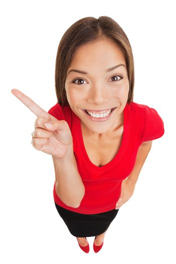 Pointing showing woman. Humorous high angle studio portrait of a grinning woman pointing to the left of the frame with her finger. Mixed race Asian Caucasian business woman isolated on white background