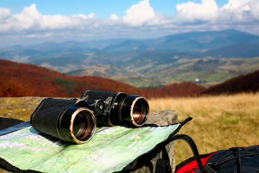 An image of binoculars and map on dry grass. Adventure theme