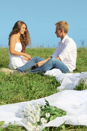 Young man and woman sitting on green field and talking