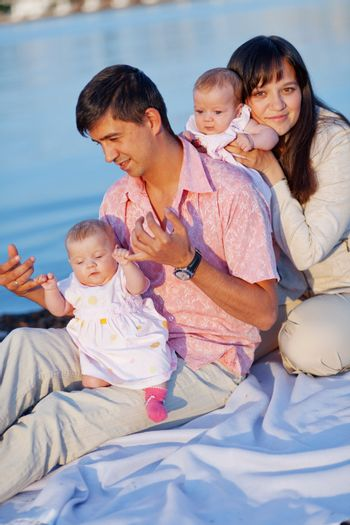 Happy young family with infant daughters over sea