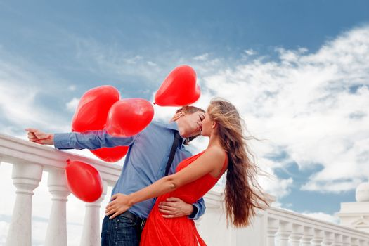 Teenage couple embracing over sky and holding bunch of baloons-hearts