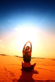 yoga girl in the heart sign on desert sand
