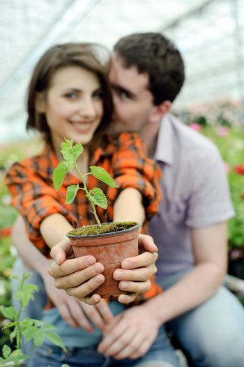 An image of a young couple with a plant in the pot