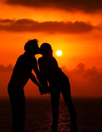 Happy couple romantically kissing at warm summer evening