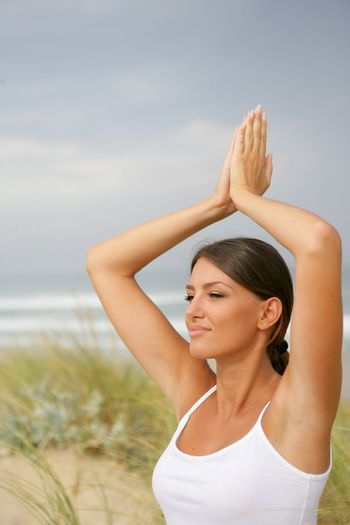 Woman doing yoga in the dunes
