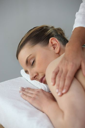Young woman being massaged in beauty parlor