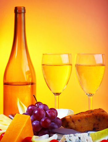 Romantic dinner, wine and cheese table setting, celebrating holidays, food still life over warm yellow studio light