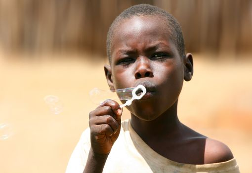 Portrait of African kid playing a bubbles. Editorial use only