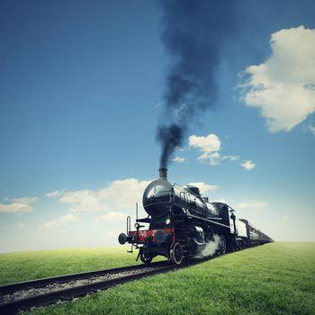 steam engine train crosses a green lawn