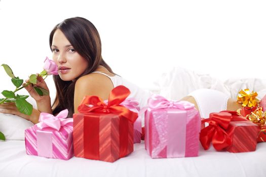 Portrait of beautiful woman with rose and gifts on bed in morning