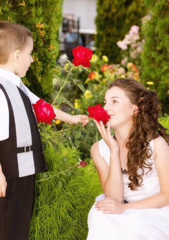 Little boy giving a rose to a beautiful girl