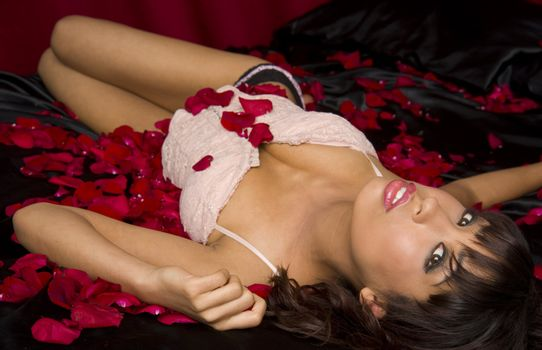 Woman laying in red rose petals