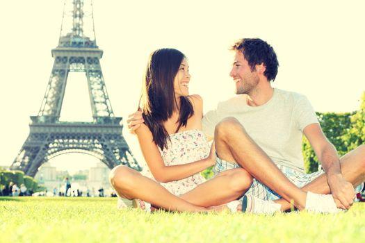 Travel tourists couple at Eiffel Tower Paris smiling happy during Paris traveling trip. Beautiful young joyful interracial couple sitting on Champ de Mars having fun. Retro vintage style processed.