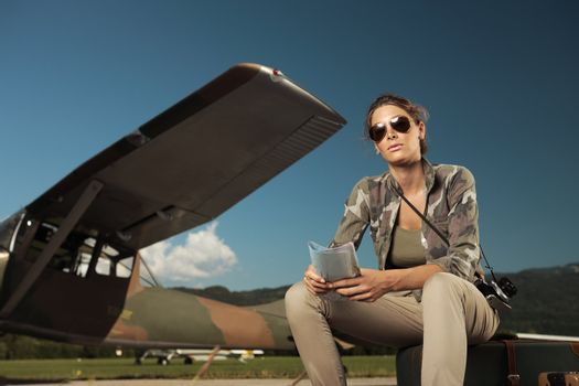 Beautiful young woman sitting on a suitcase at the airport. Airplane in the background