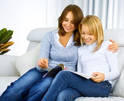 Mother with Teenage Daughter reading fashion Magazine