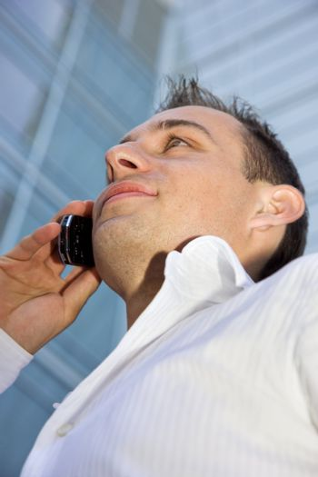 handsome businessman with cell phone in front of a modern office building (focus on lips)