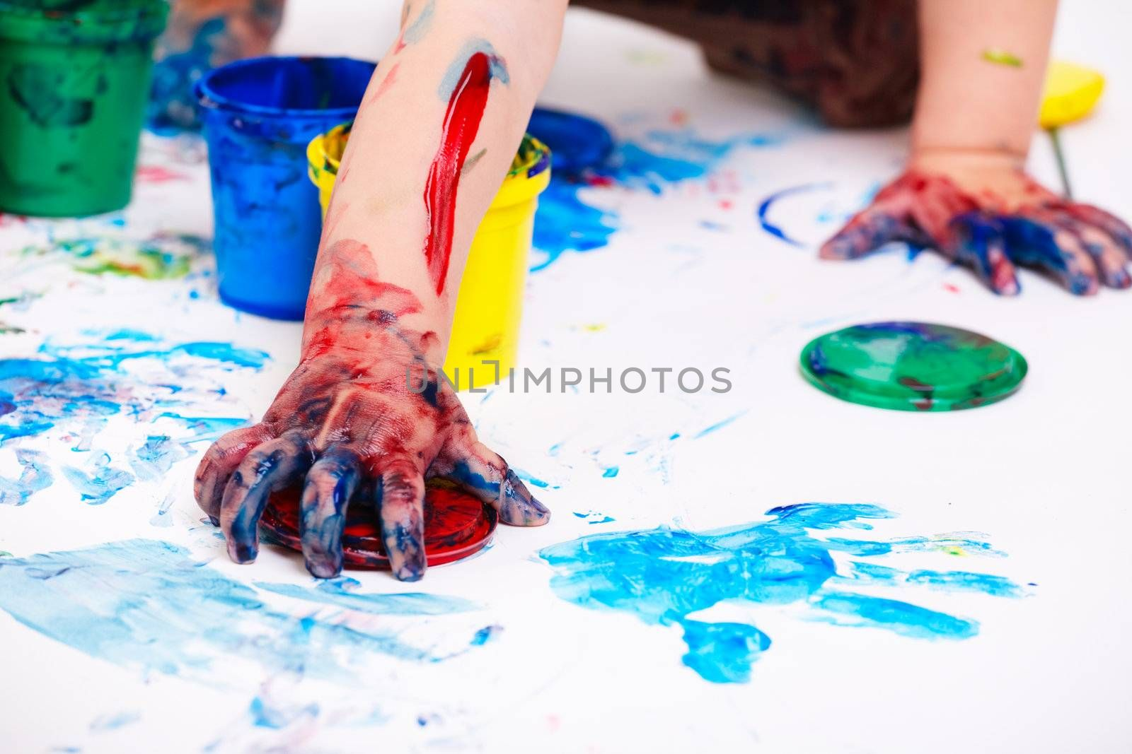Closeup of colorful finger paints over white background