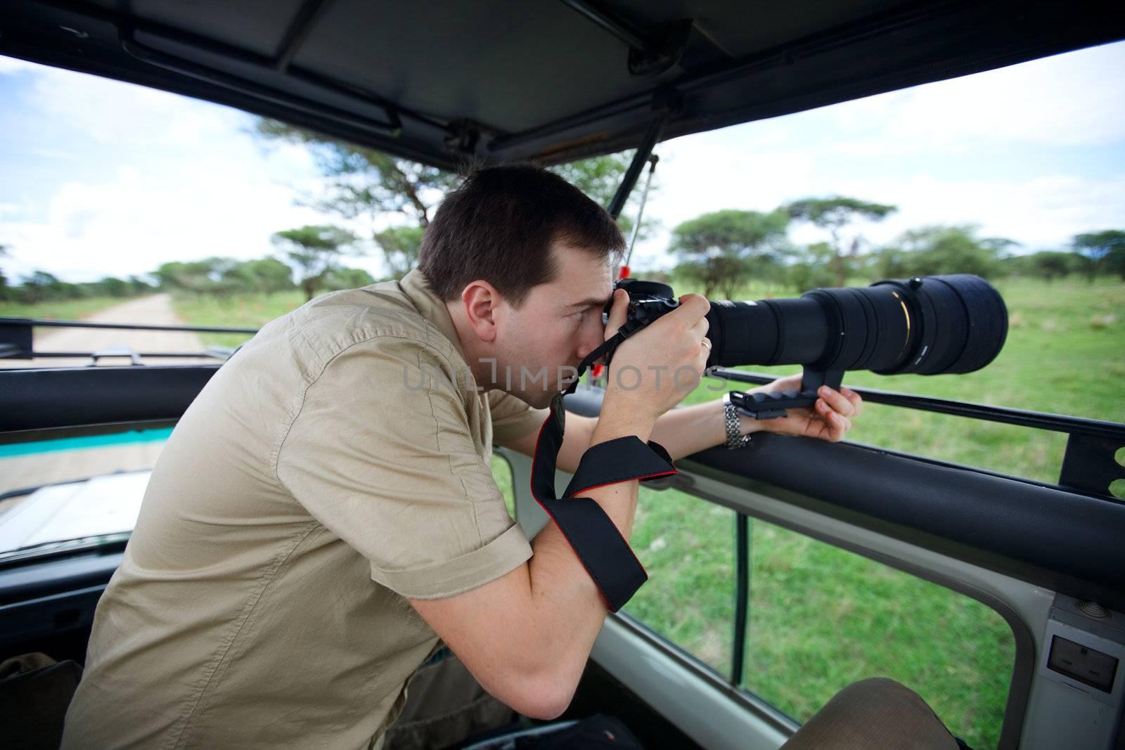 Safari vacation. Professional photographer taking picture on game drive in Tarangire national park, Tanzania.