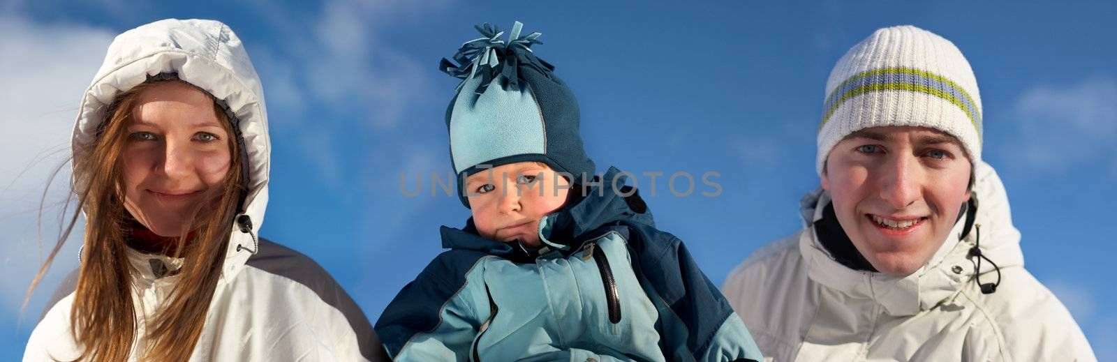 Young family of three in winter clothes over blue sky