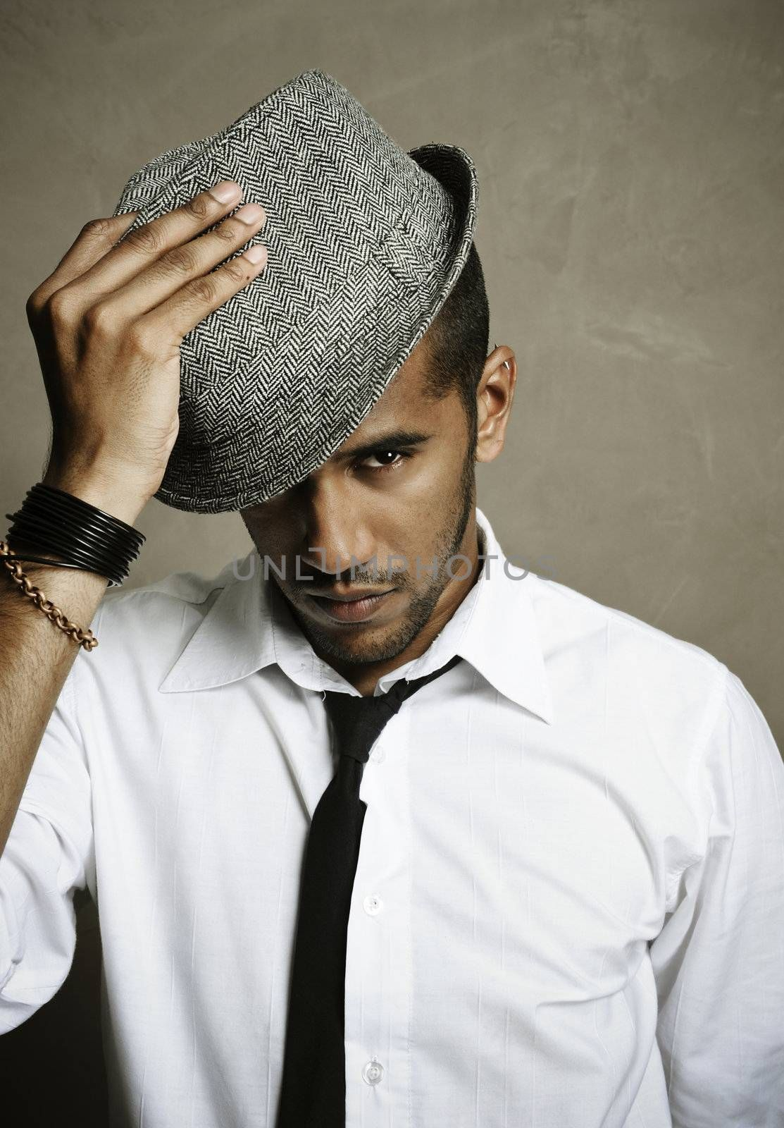 Male model stares at camera with hand on hat
