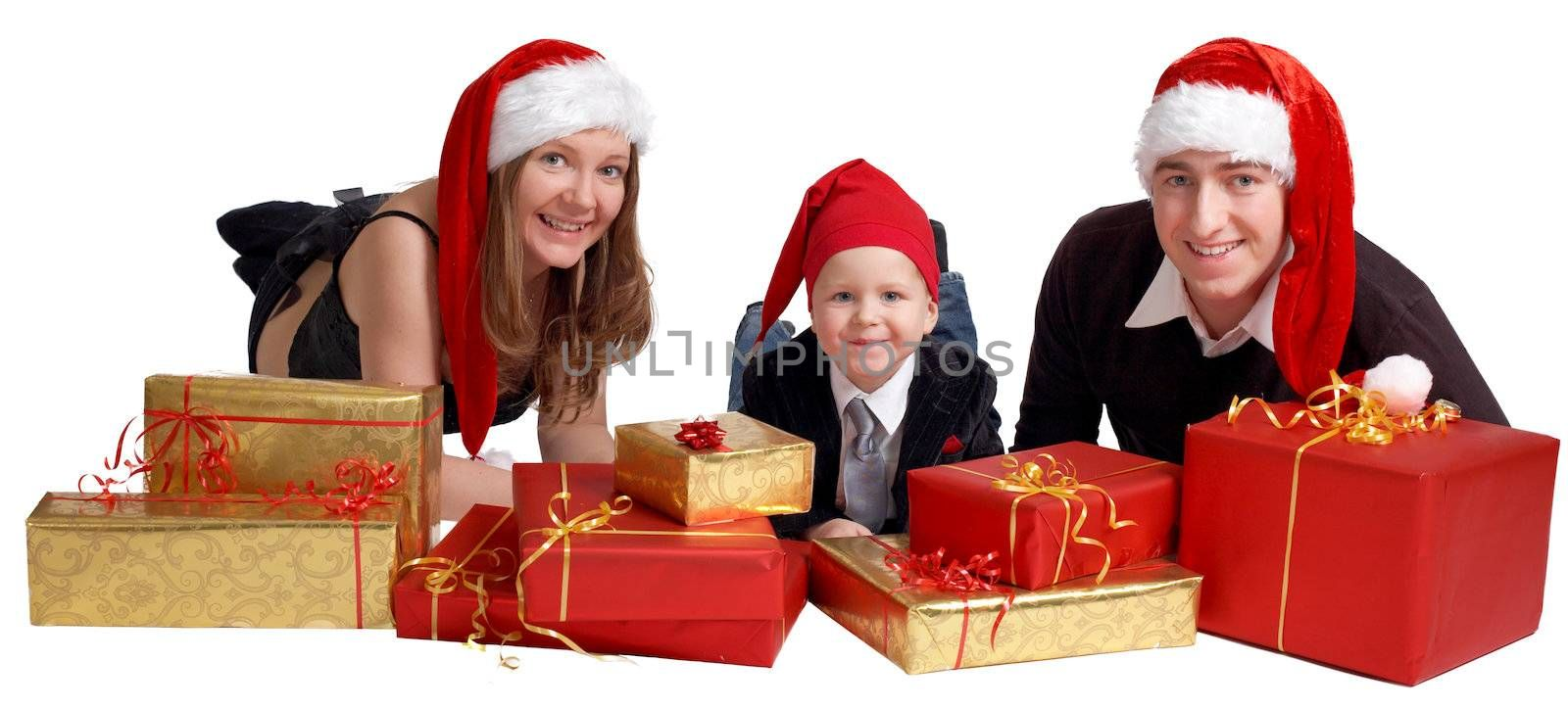 Isolated studio shot of happy young family of three wearing Santas hats with a lot of Christmas presents.