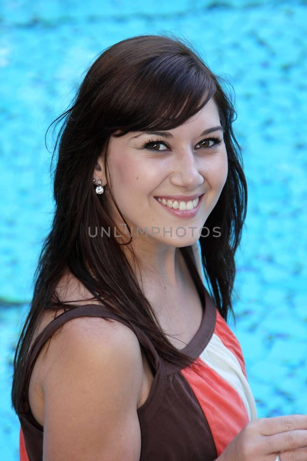 Beautiful brunette girl relaxing next to the swimming pool