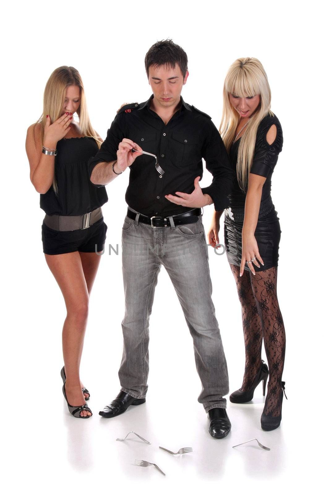 Magician make performance with twisted fork with two beauty girls
