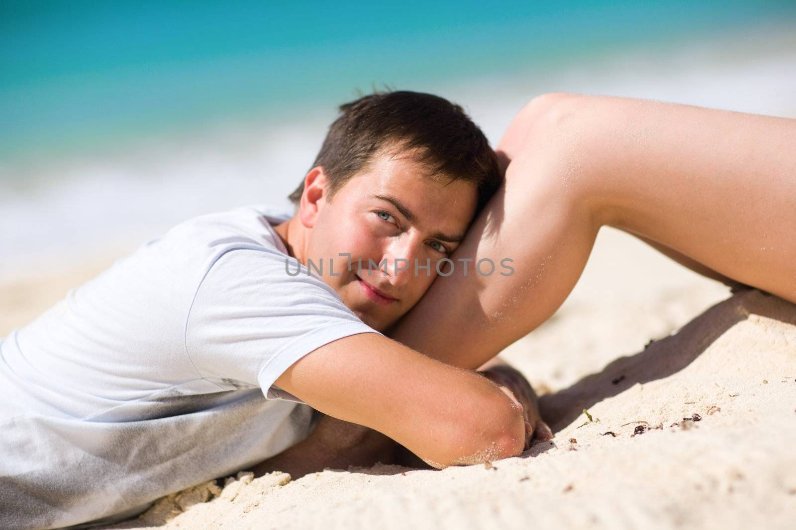 Happy handsome man on tropical beach at sunny day