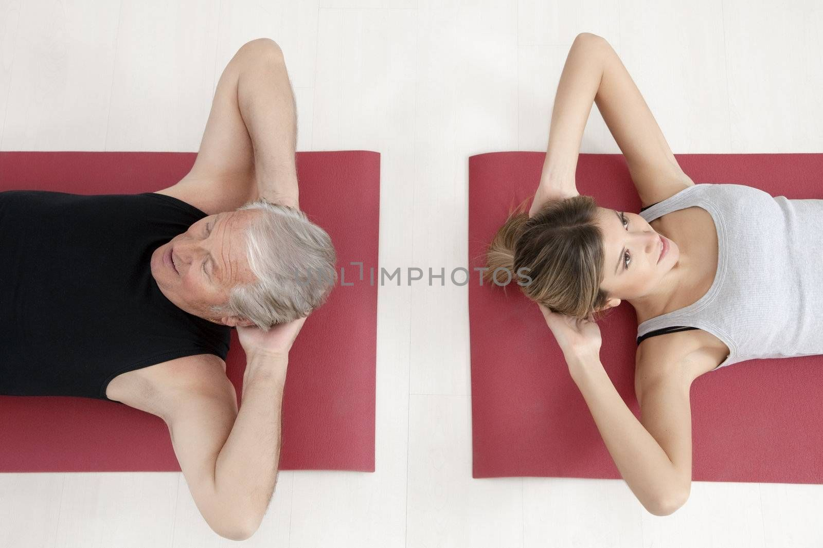 young woman and senior adult exercising in gym