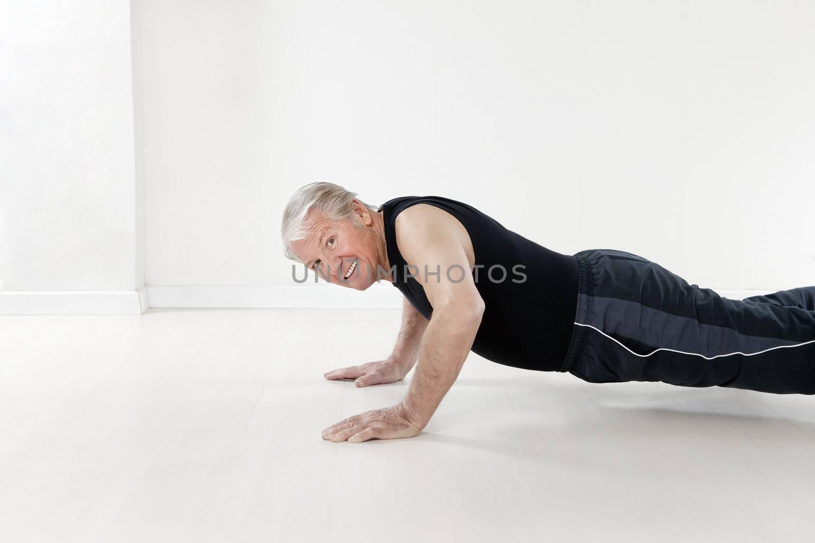 side view of senior man doing push-ups