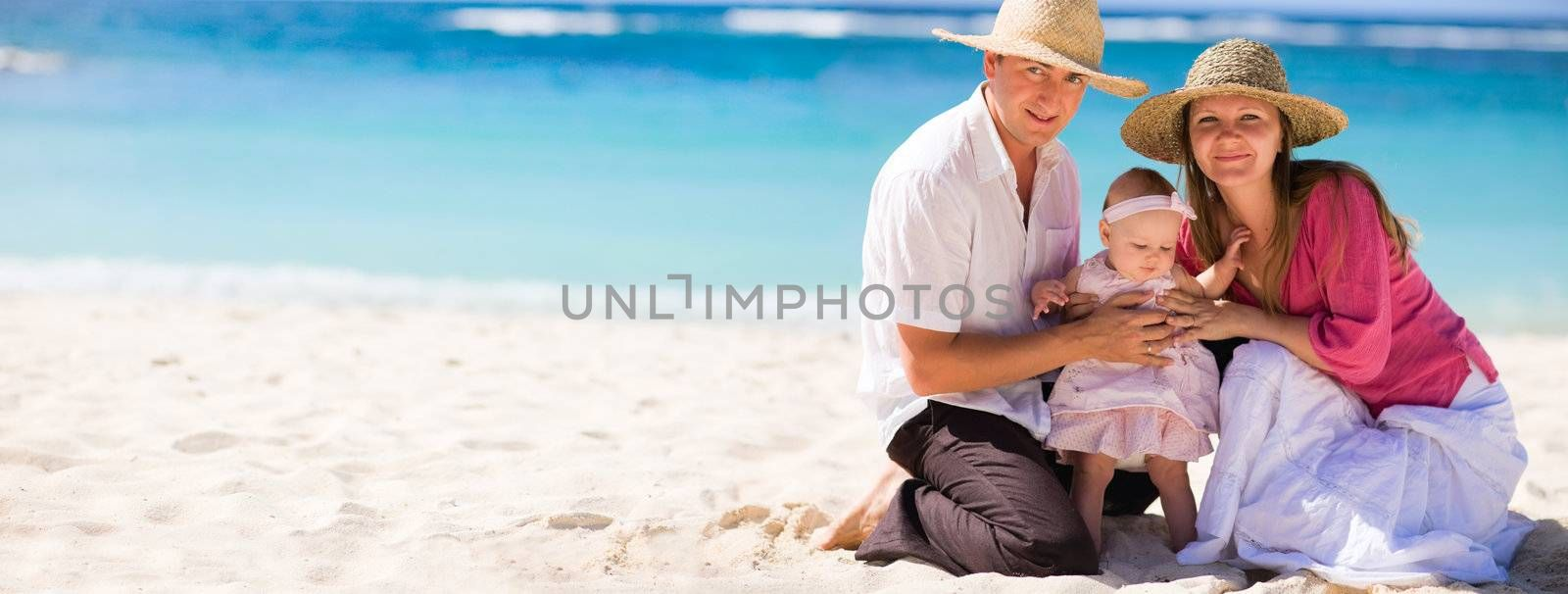 Family vacation. Young family of three on white sand tropical beach