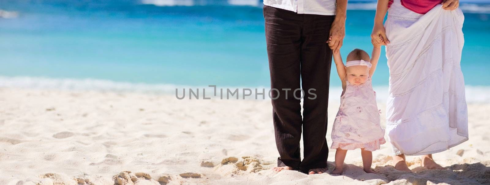 Family vacation. Young family of three on white sand tropical beach.