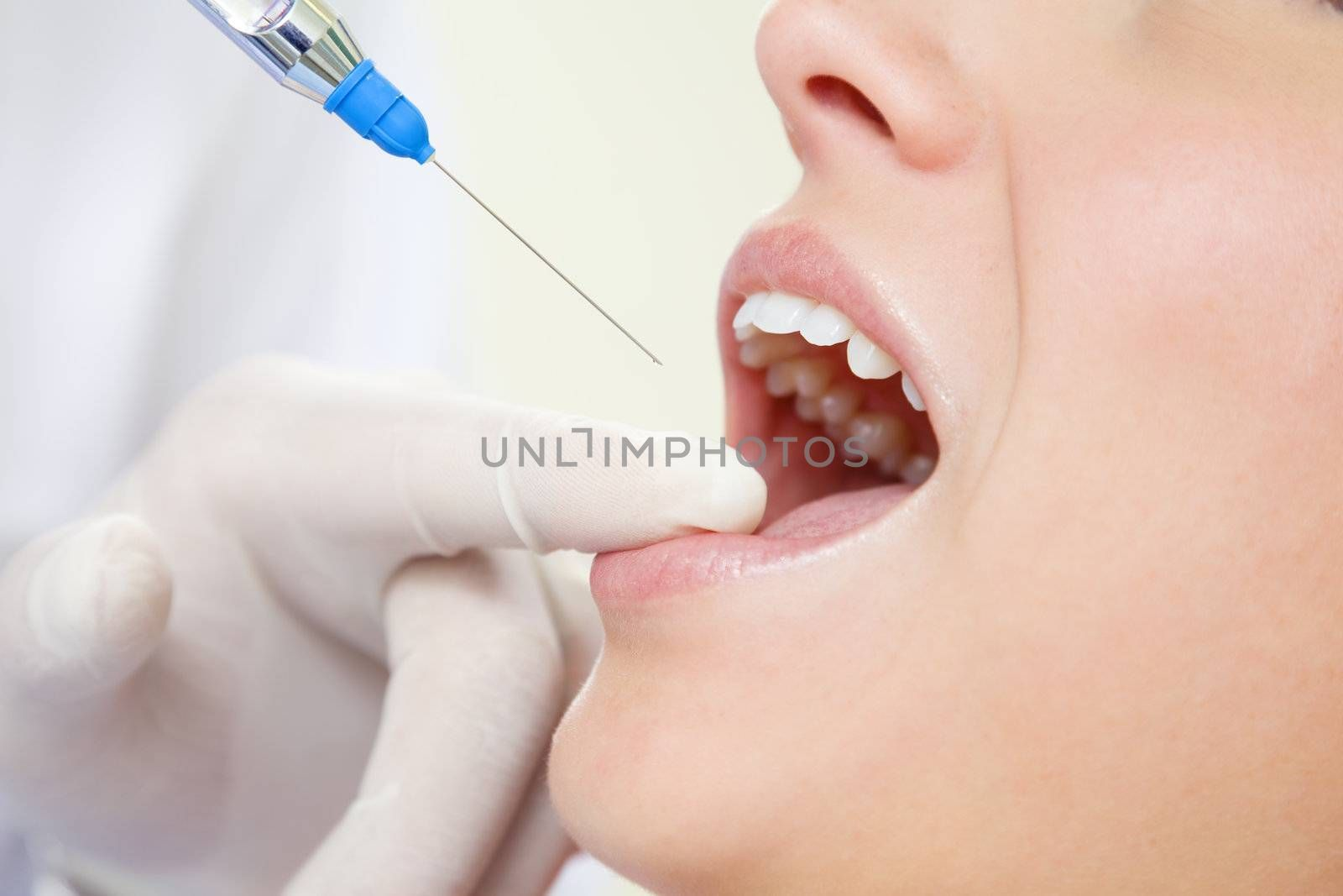 dentist holding a syringe and anesthetizing his patient