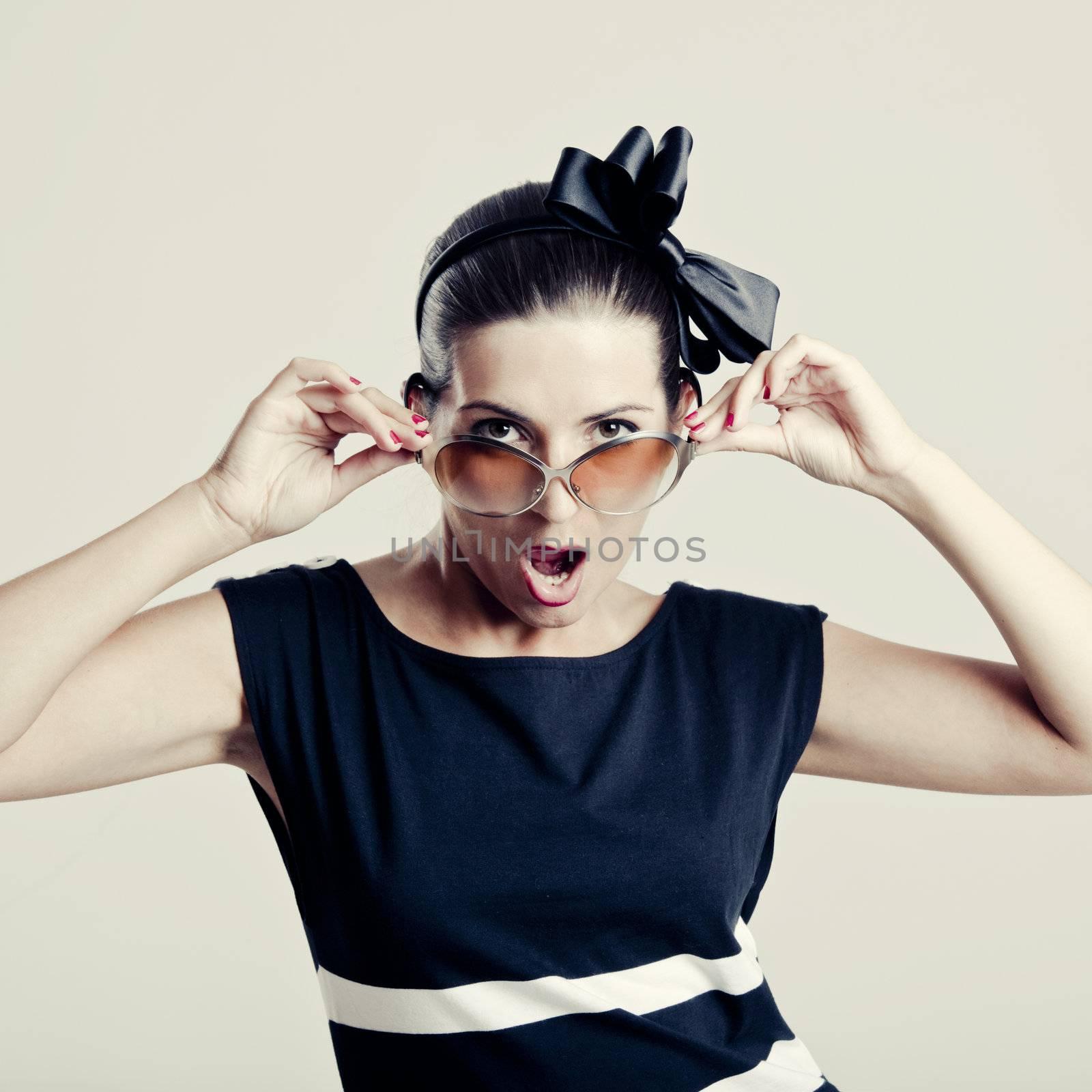 Portrait of a beautiful fashion woman posing with sunglasses