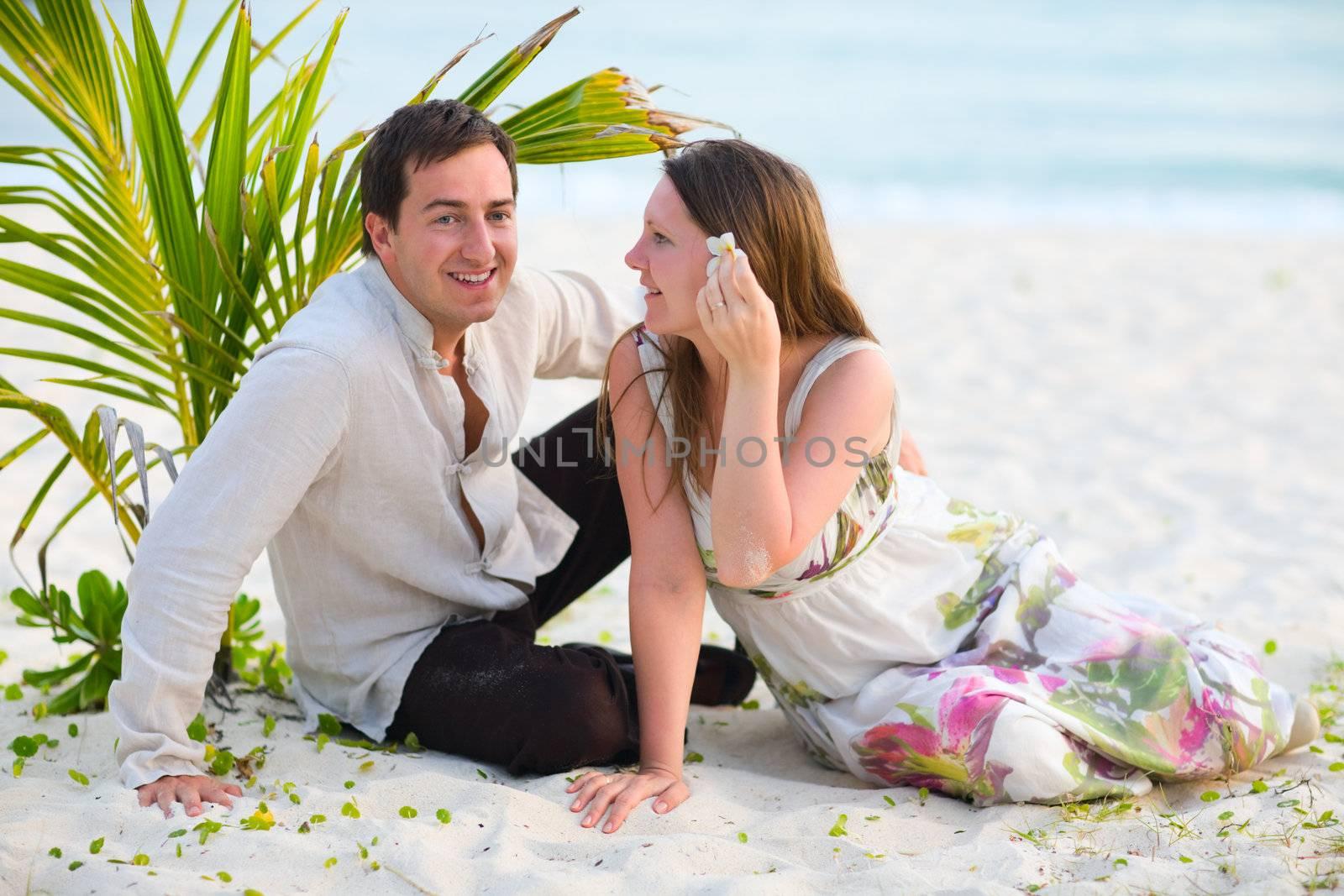 Romantic couple on white sand tropical beach.