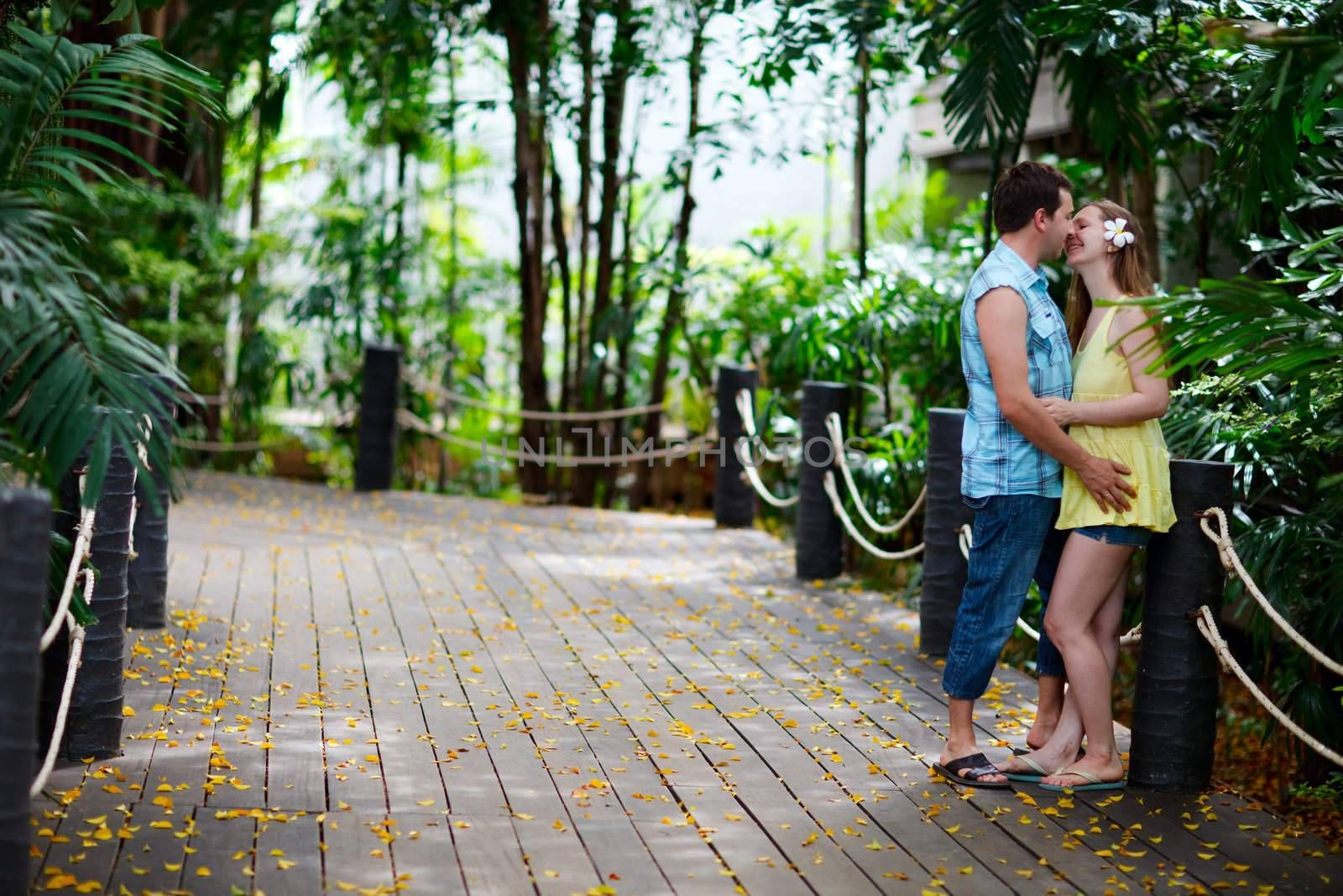 Young romantic couple kissing outdoors at summer day