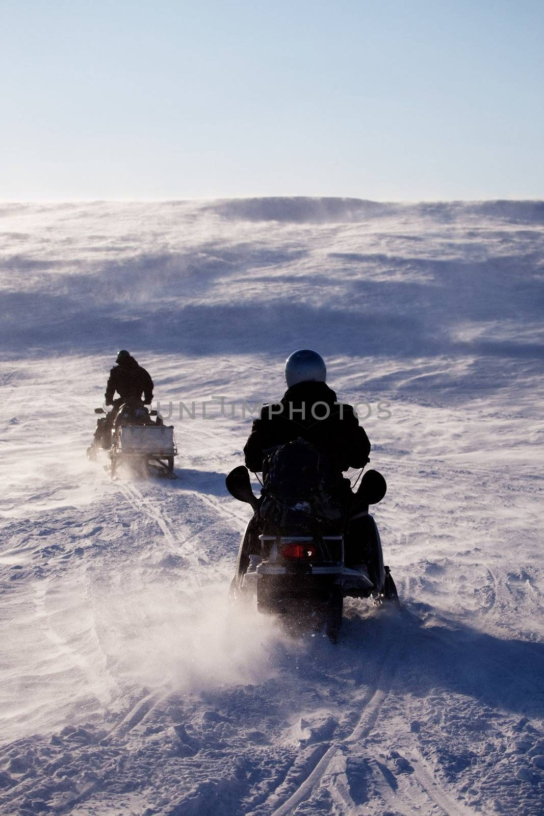 Two people riding up a hill on snowmobiles