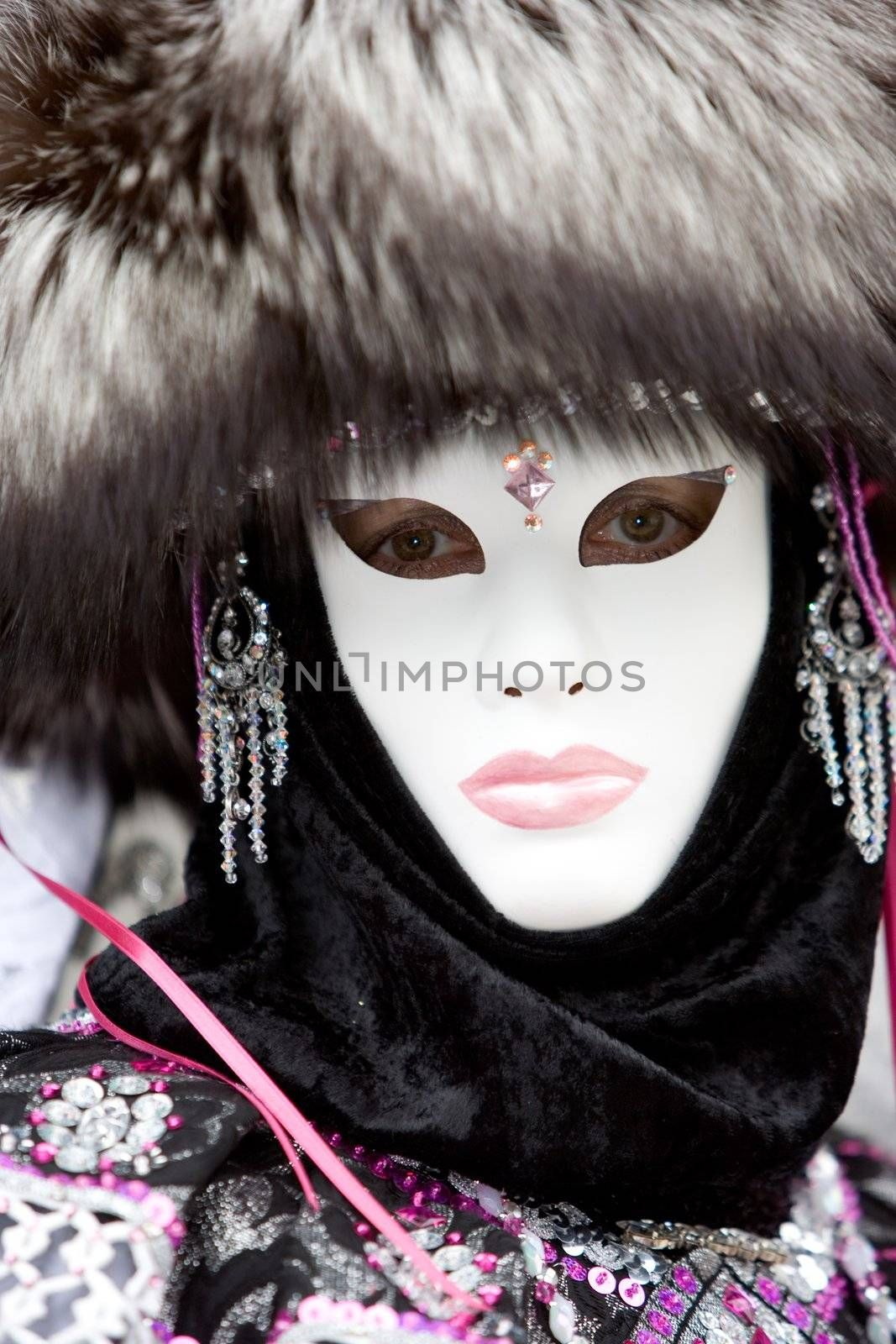 Lady at the Venice carnival wearing a fox hair hat, jewelery and a white mask