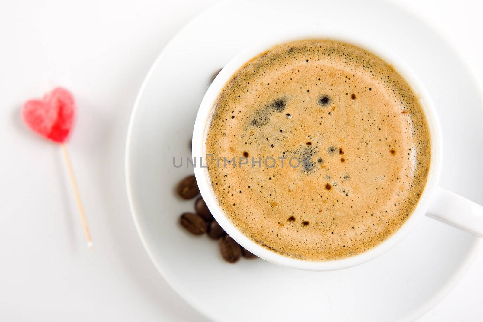 Cup of coffee on white with candy heart on background, focus on liquid