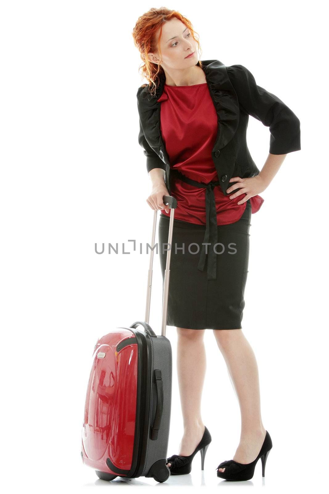Young redhead businesswoman (deaf with hearing aid) with red suitcase, isolated on white background