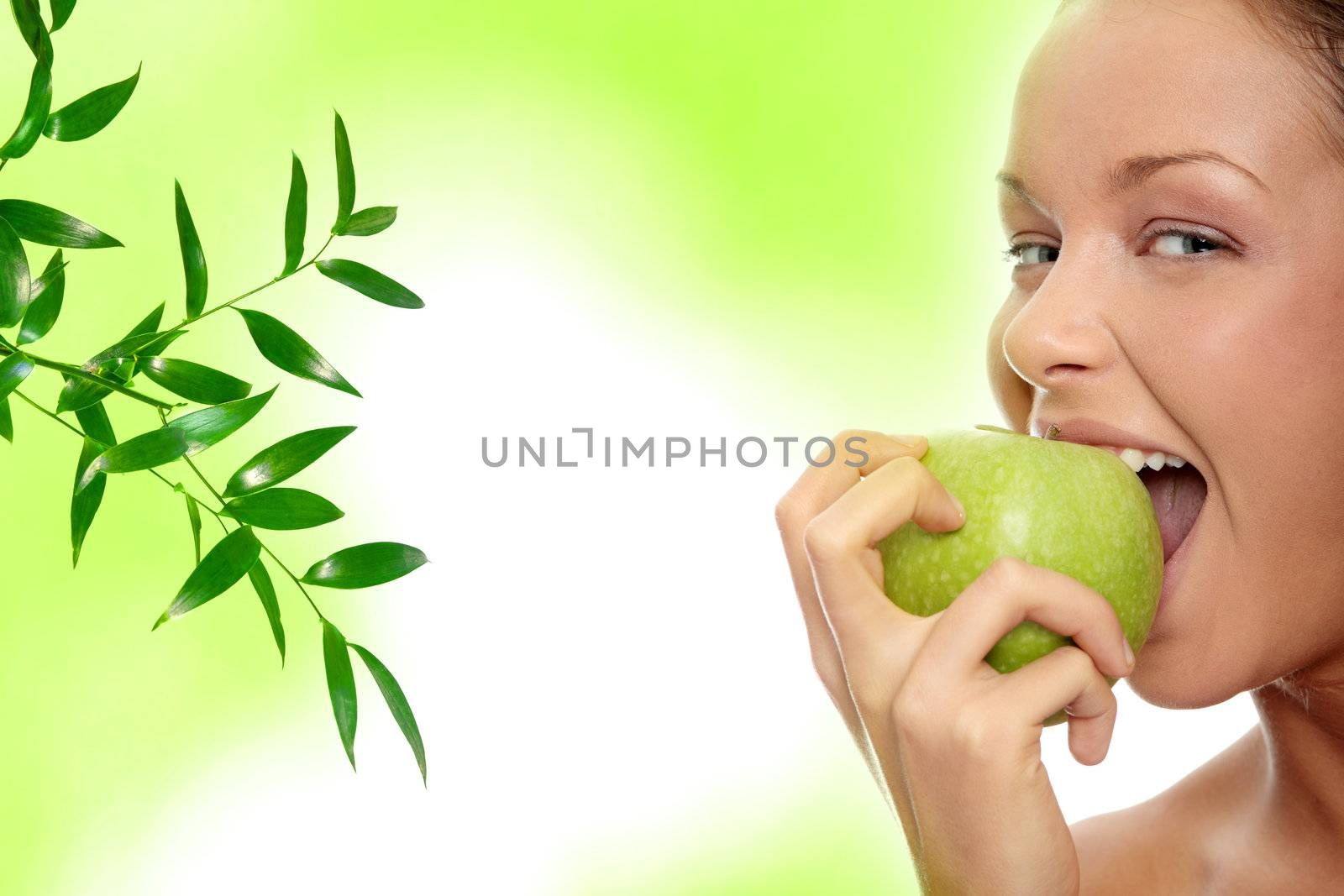 Caucasian beauty with green apple, against abstract green background