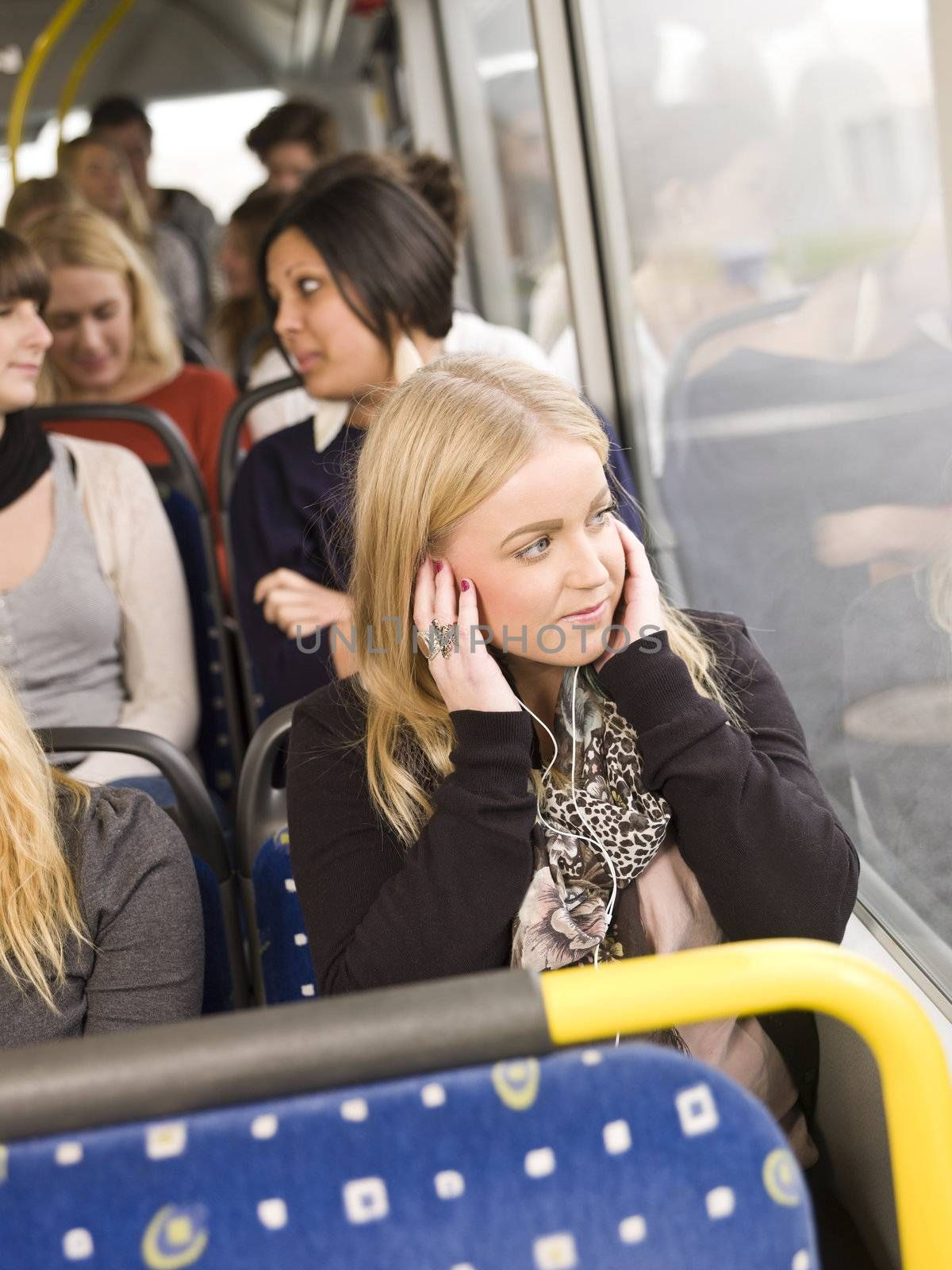 Woman listen to music while going by the bus