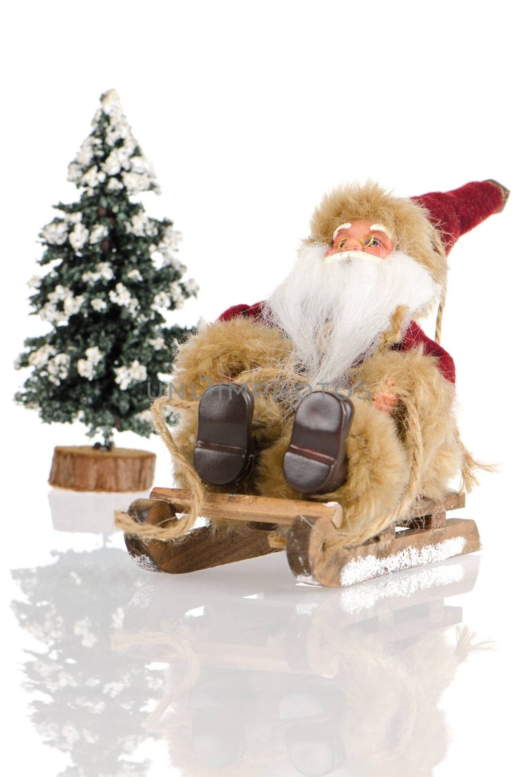 Miniature of Santa Claus on sleigh and a pine tree with snow, on white reflective background.