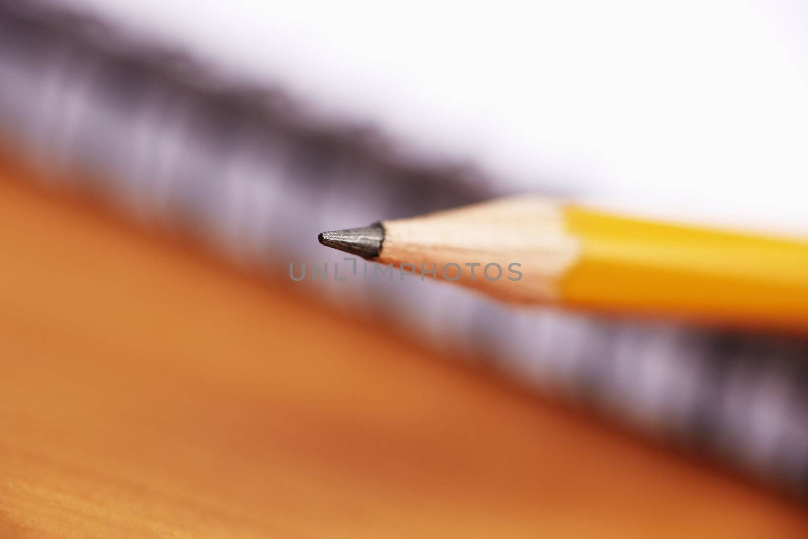yellow pencil, selective focus on writing part (center of photo)